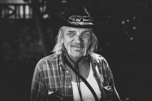 alter Mann mit cowboyhut und offenem Hemd, schwarz-weiß Bild