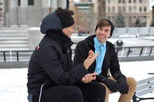 Zwei junge Männer unterhalten sich auf Parkbank im Winter