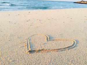 Herz in Sand gemalt, dahinter ist das Meer