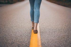 Füße einer Frau gehen auf Mittelstreifen einer Straße