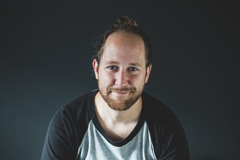 Mann mit schütterem Haar und Bart lächelt in Kamera, schwarzer Hintergrund