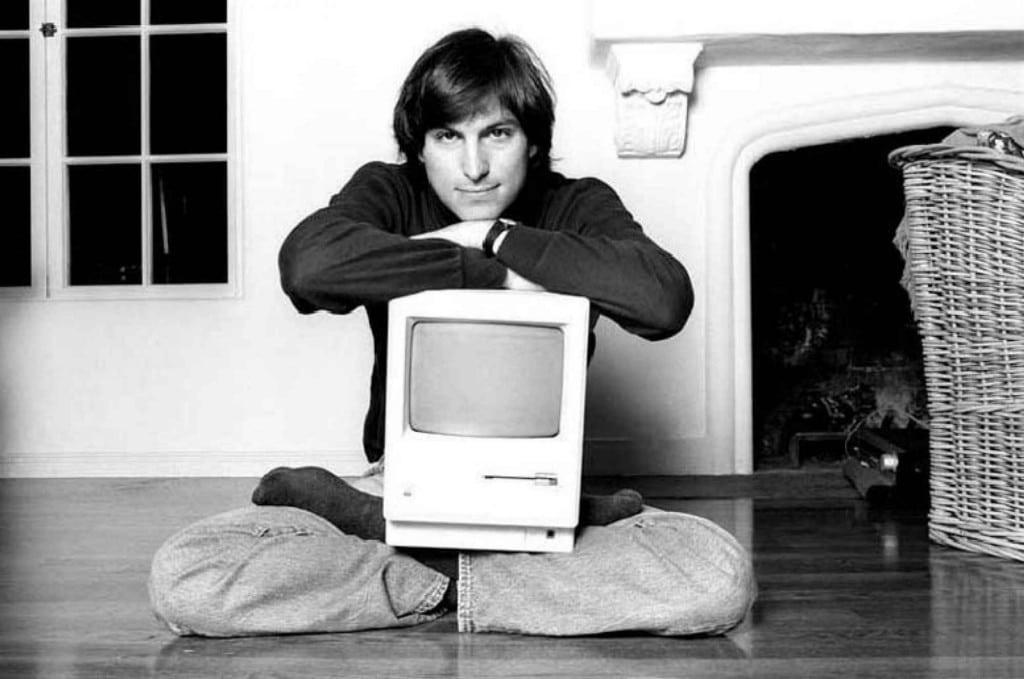 Steve Jobs sitzt mit seinem Computer auf dem Schoß auf dem Boden