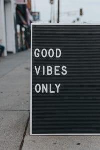 """Schriftzug """"GOOD VIBES ONLY"""" auf Tafel am Gehsteigrand"""