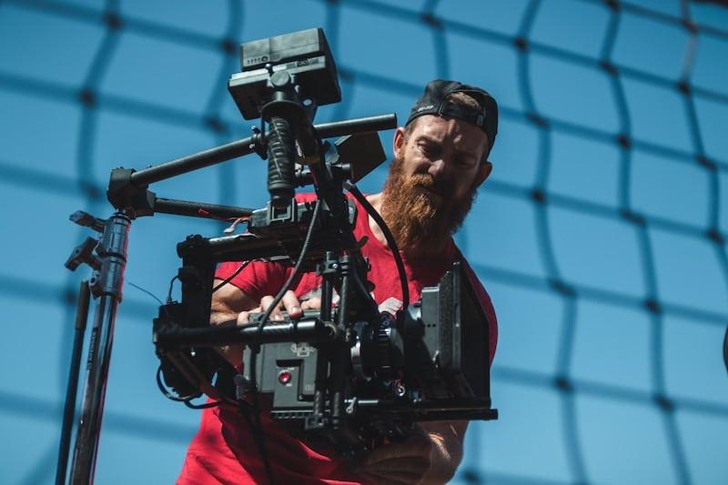 Mann mit Filmkamera hinter Netz